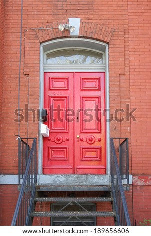 Red front door with metal stairs
