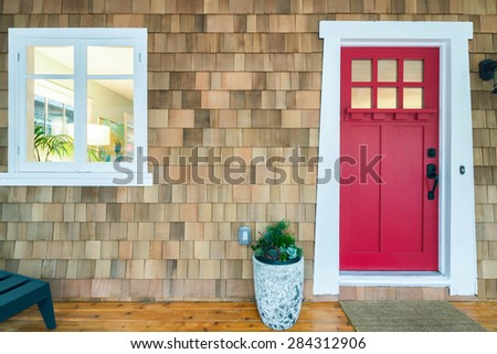 Red front door with window and flower pot.  - stock photo