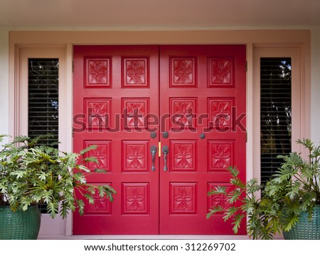 Red front doors with flower carvings at the entrance to an upscale home with Philodendron plants on each side. - stock photo