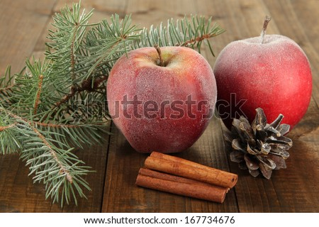 Red frosted apples with fir branch and bumps on wooden background