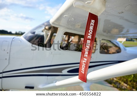 Red fuel safety ribbon on wing of airplane. Remove before the flight - stock photo
