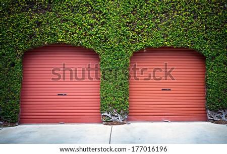 red garage door with green plants - stock photo