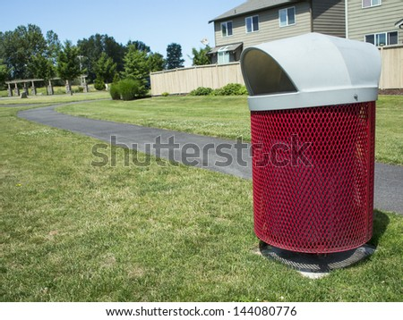 Red garbage can with walking path and suburban houses in the background.