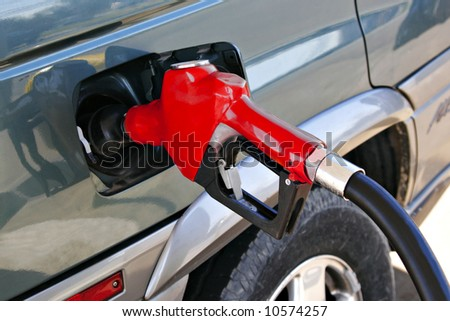 red gasoline pump nozzle - stock photo