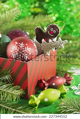 Red gift box full of Christmas and New Year toys, baubles and decorations on green defocused background, with natural conifer branches and bokeh lights, vertical composition - stock photo