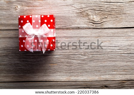 red gift box, polka dots, on wood background - stock photo