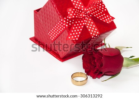 Red gift box with a red rose and golden ring.