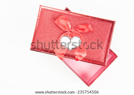 Red gift box with big bow ribbon on white background - stock photo