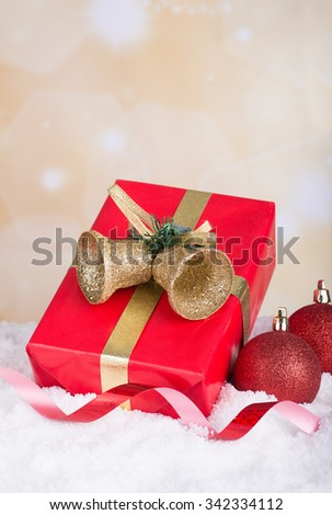 Red gift box with Christmas ornaments on snow with holiday background - stock photo