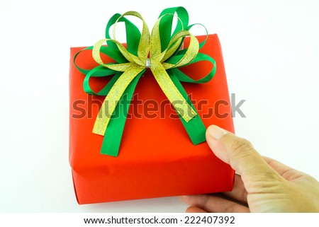 Red gift box with green and gold ribbon in hand isolated on white background - stock photo