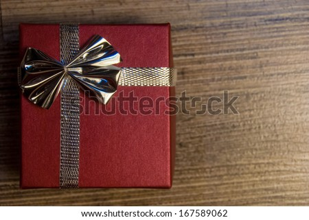 red gift box with ribbon and bow on wood - stock photo