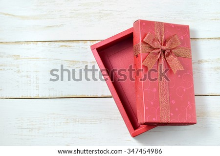 Red gift box with ribbon bow opened on vintage white wooden table - stock photo