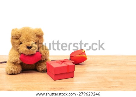 Red gift box with tulip and teddy bear on wooden table and copy space