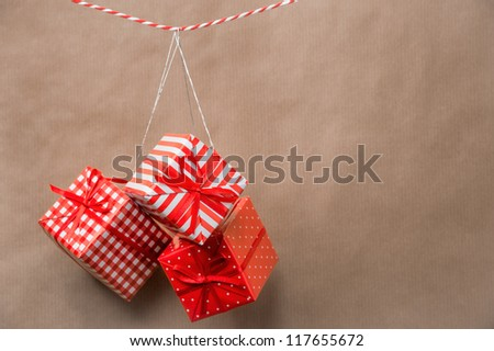 Red gift boxes hanging on a ribbon. Old brown paper background - stock photo