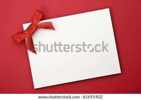 red gift tag tied with a bow of red satin ribbon - stock photo