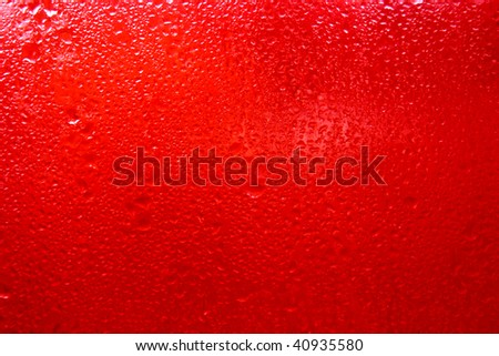 red glass with drops of water - stock photo