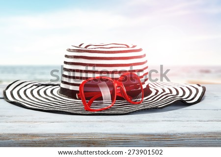 red glasses and hat on desk of blue color  - stock photo