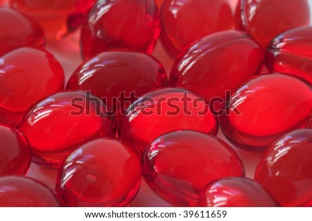 Red glossy transparent vitamin E pills