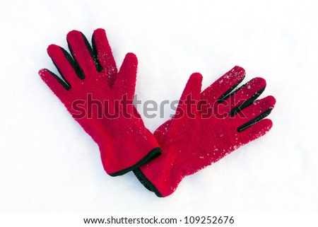 red gloves on snow surface - stock photo
