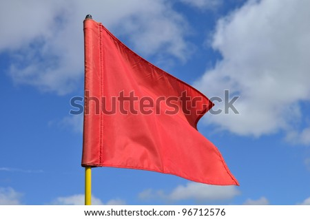Red Golf Flag Waving in the Breeze - stock photo