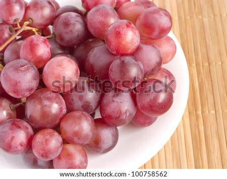 Red grape berries in white plate on straw tray closeup - stock photo