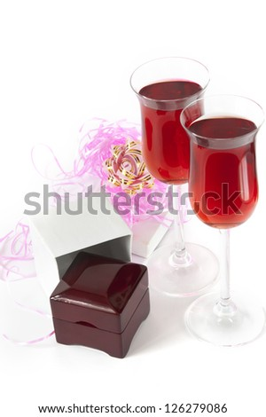 red grape wine at crystal glasses and jewelery box, expensive gift