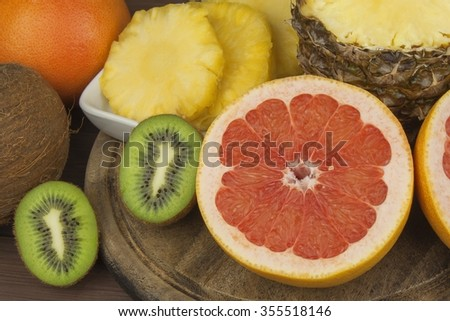 Red grapefruit and fruit for weight loss. Fresh dietary food for athletes. Fruit on a wooden table. Composition with variety of fresh fruits. Balanced diet. Assortment of exotic fruits.  - stock photo