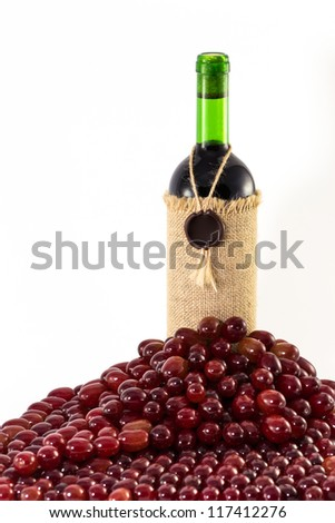 Red grapes around fabric-wrapped wine bottle isolated on white background - stock photo