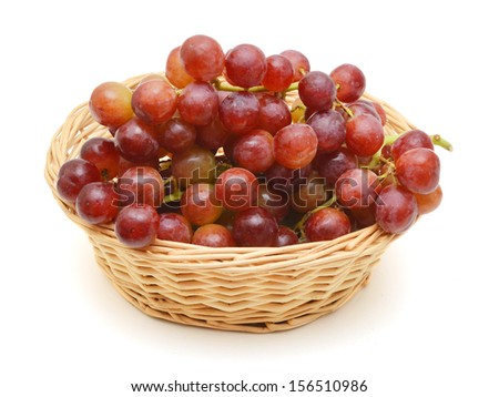 red grapes in basket on white background  - stock photo