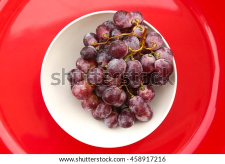 Red grapes in white bowl on red background