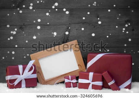 Red, Gray Christmas Decoration On Snow, Snowflakes, Christmas Gifts, Presents. Picture Frame. Copy Space For Advertisement. Rustic, Vintage Wooden Background. Festive Snowy Card. Black And White Image - stock photo