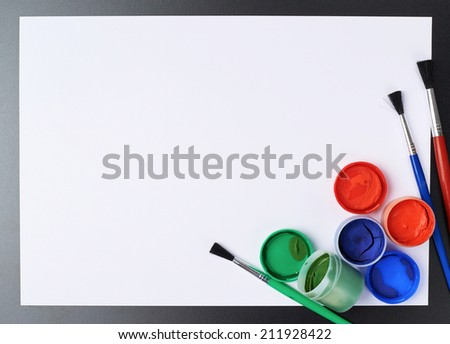 Red, green and blue gouache paint and brushes over the white paper sheet as a copyspace background composition - stock photo