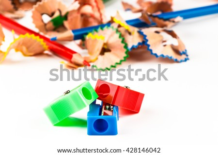 Red, green and blue pencil sharpener with color shavings pencils. Horizontal image.