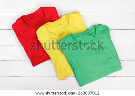 Red, green and yellow folded t-shirts on white wooden background - stock photo