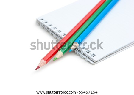 red  green blue pencils and notebook isolated on a white  background