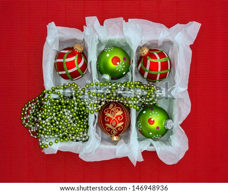 Red & green Christmas ornaments in a box on textured red background.  - stock photo
