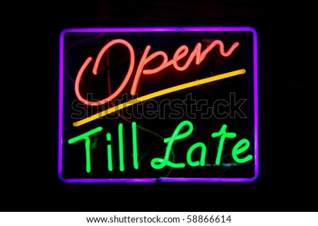 Red, green, purple and yellow neon sign of the words 'open till late' on a black background. - stock photo