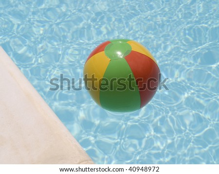 red green yellow beach ball floating in a swimming pool near the edge. - stock photo