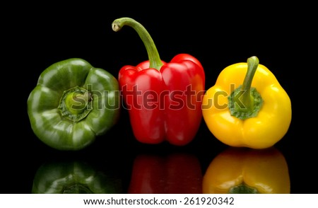 Red,green,yellow bell peppers isolated on black background - stock photo