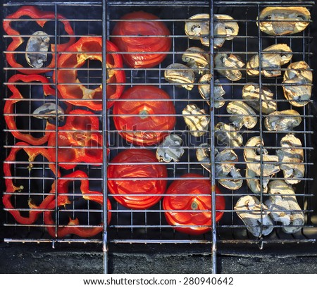 Red grilled pepper, tomato and mushrooms on bbq fireplace