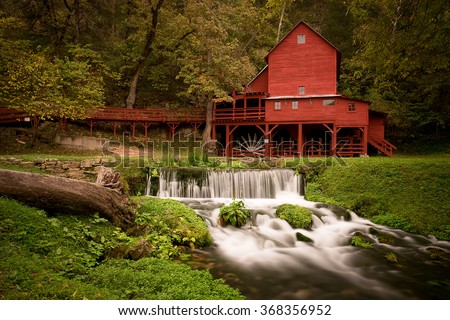 Red gristmill and waterfall located in rural Missouri. - stock photo