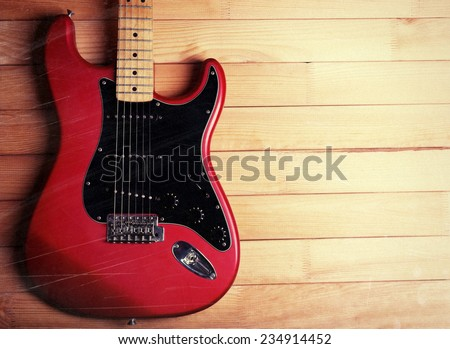 Red guitar on wooden background