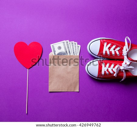 red gumshoes, heart shaped toy and money on the purple background - stock photo