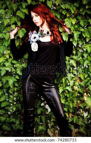 red hair fashion woman in black with fashion accessories against wall with green rambler plant - stock photo