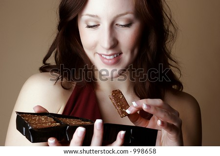 Red hair female holding a piece and a box of chocolate