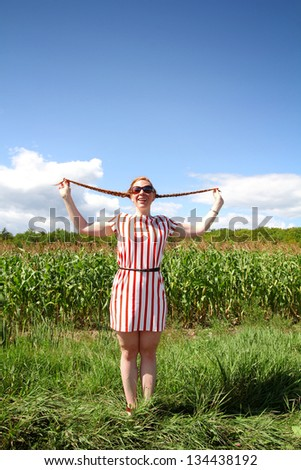 Red hair girl holding braids in hands in a field - stock photo