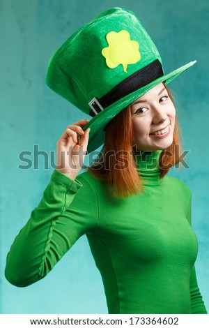 Red hair girl in Saint Patrick's Day party hat having fun isolated on green grunge background