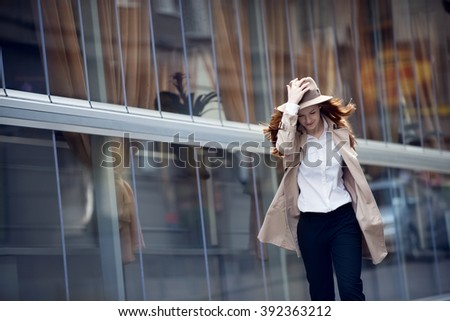 red hair woman in a hat is crossing the street
