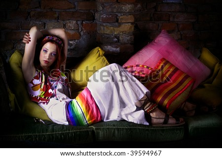 red hair woman in oriental clothes resting on sofa - stock photo