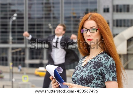 Red hair woman posing on jumping businessman background